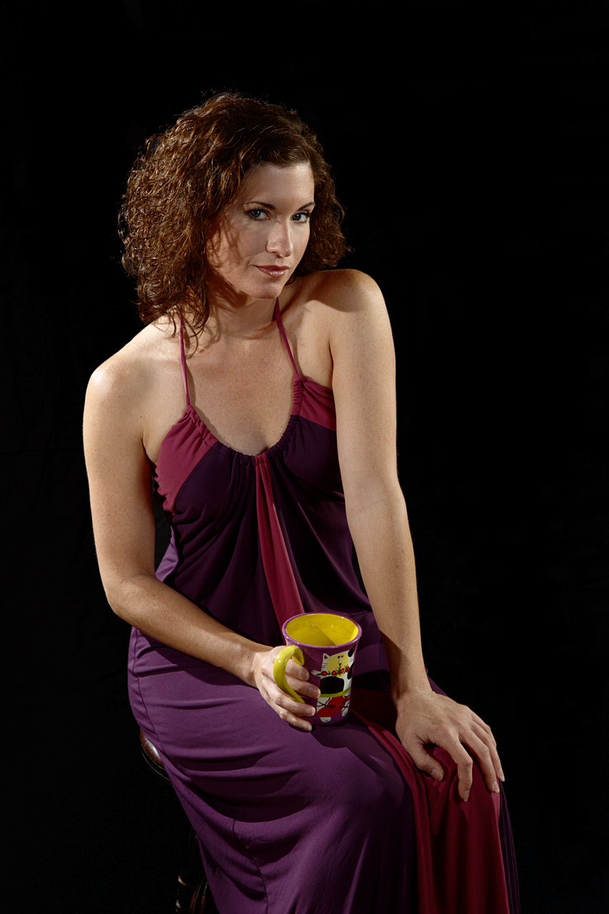 Black background behind a woman in purple dress holding a coffee cup