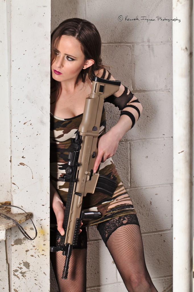 Woman in an old industrial building holding a gun, looking around the corner