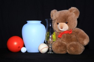 Still life lit with on-camera lighting with three balls, two vases, and a Teddy bear. There are nearly no shadows.