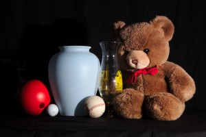 Front-45 degree lighting for a still life with three balls, two vases, and a Teddy bear. Shadows show the shape of objects.
